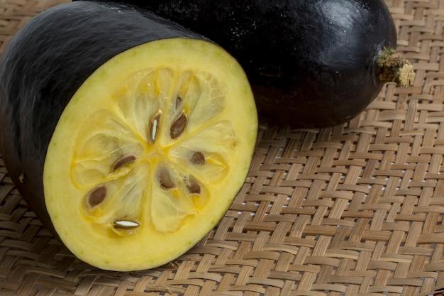 O jambolão de frutas exóticas fatiado na peneira de vime
