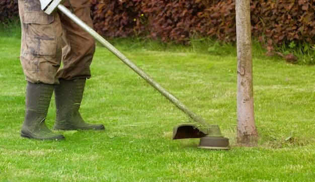 O jardineiro corta um gramado verde com um cortador de grama portátil.