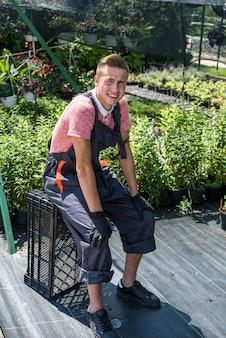 O jardineiro está cuidando das plantas enquanto cuida das flores em uma estufa