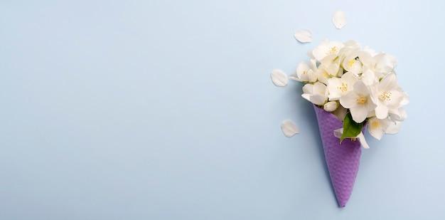 O jasmim floresce em um vidro de waffle no azul com um espaço da cópia.