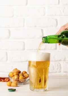 O jato de cerveja da garrafa é derramado em um copo de cerveja, causando muitas bolhas e espuma, fundo de parede de tijolo branco