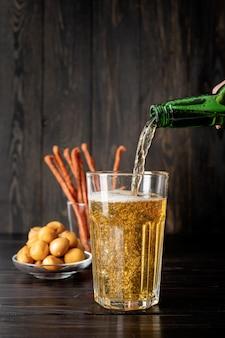 O jato de cerveja da garrafa é despejado em um copo de cerveja, causando muitas bolhas e espuma, fundo preto de madeira