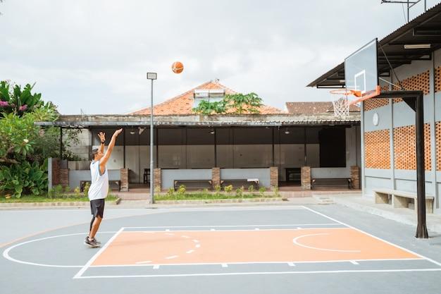 O jogador de basquete chuta o lance livre para o aro enquanto pratica