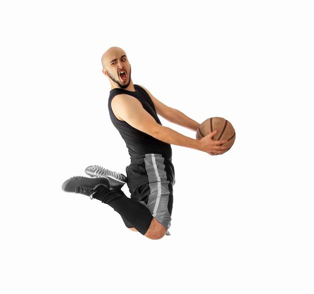 O jogador de basquete faz uma enterrada no branco. o jogador de basquete faz enterrada.