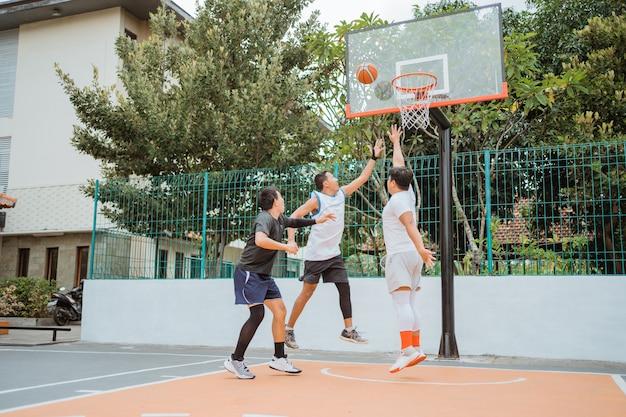 O jogador de basquete pulando na posição de rebote enquanto joga