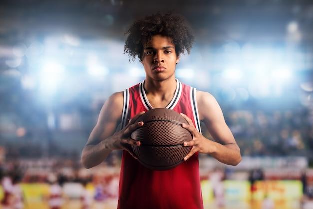O jogador de basquete segura a bola na cesta no estádio cheio de espectadores.