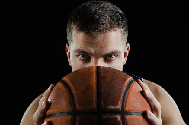 O jogador de basquetebol cobrindo o rosto com uma bola