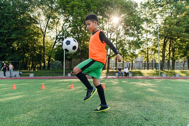 O jogador de futebol adolescente habilidoso focado enfia a bola de futebol na perna.
