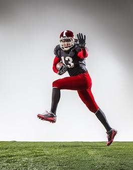O jogador de futebol americano em ação na grama verde e fundo cinza.
