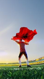 O jogador de futebol após o campeonato do jogo vencedor segura a bandeira da albânia. estilo de polígono