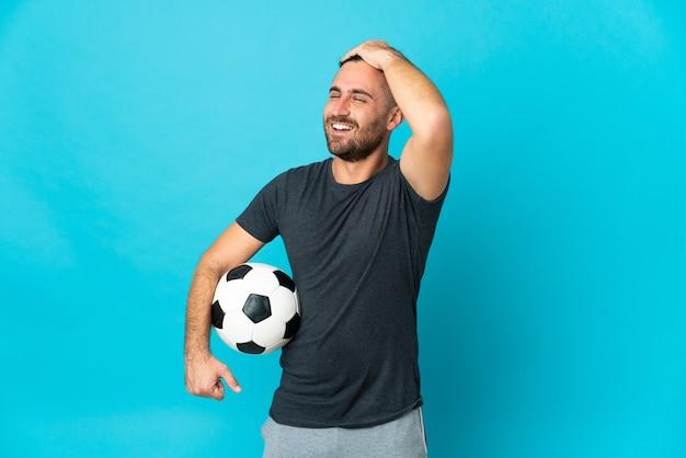 O jogador de futebol isolado em um fundo azul percebeu algo e pretende a solução