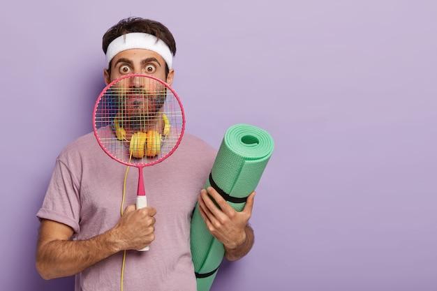 O jogador de tênis chocado olha pela raquete, segura o karemat, usa roupas esportivas, pronto para jogar ao ar livre com um amigo