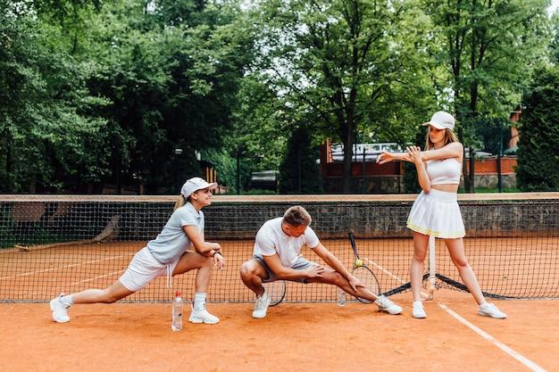 O jogador de tênis masculino do instrutor e a mulher dois esticam antes de jogar. jovem equipe juntos.