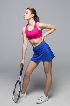 O jogador de tênis novo bonito da mulher da aptidão do esporte faz os exercícios isolados.