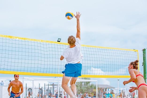 O jogador de vôlei de praia é um atleta masculino que se prepara para servir a bola na praia.