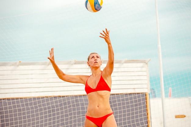 O jogador de vôlei de praia é uma atleta de vôlei se preparando para servir a bola na praia.