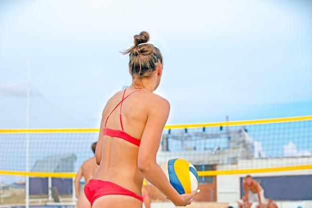 O jogador de vôlei de praia é uma atleta feminina que se prepara para servir a bola na praia.