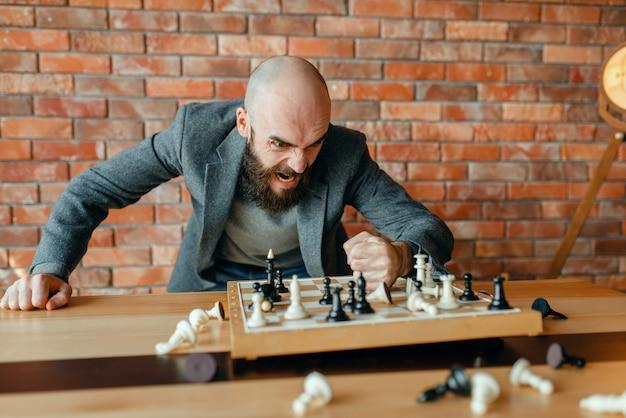 O jogador de xadrez com raiva bate o punho no tabuleiro com as peças.