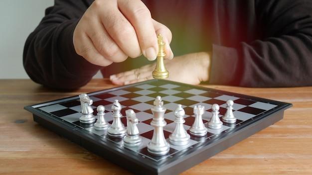 O jogador de xadrez pega o xadrez do rei dourado no tabuleiro de xadrez