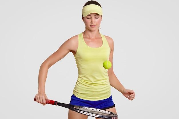 O jogador profissional do tênis fêmea novo atrativo bateu a bola de tênis com raquete, treina no gym, veste a faixa, o short e a camisa de polo, concentrou a expressão, isolada sobre a parede branca.