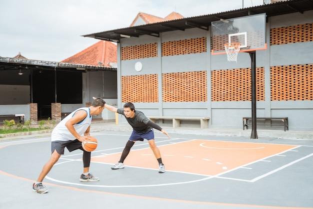 O jogador que dribla a bola vai atacar e um jogador adversário está bloqueando