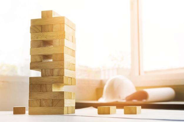 O jogo de blocos de torre de madeira com planos de engenheiro de arquitetura ou gravuras azuis, lábios e régua em mesa de madeira, plano e conceito de construção