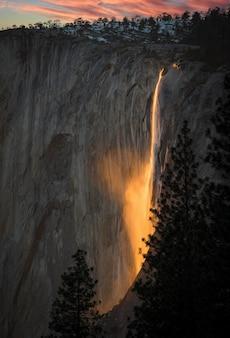 O jogo do pôr do sol com o reflexo na cachoeira do parque nacional de yosemite os faz brilhar em chamas.
