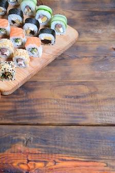 O jogo do sushi de um número de rolos é ficado situado em uma placa de estaca de madeira em uma tabela na cozinha de uma barra de sushi.