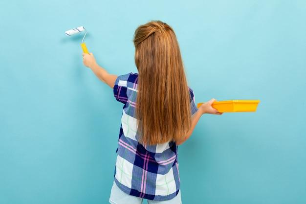 O jovem adolescente pinta uma parede azul clara com um rolo de pintura.