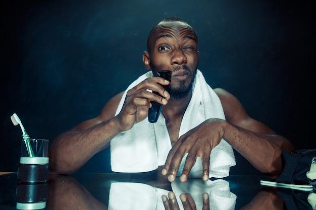 O jovem africano no quarto sentado em frente ao espelho coçando a barba em casa. conceito de emoções humanas