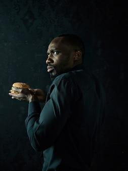 O jovem afro-americano comendo hambúrguer e desviando o olhar no estúdio preto