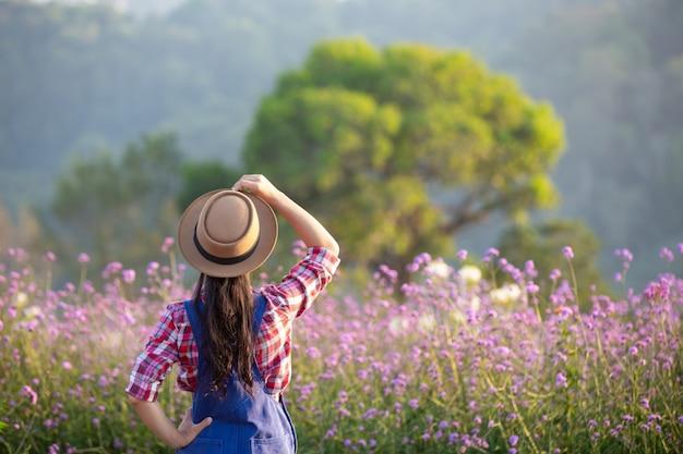 O jovem agricultor admira as flores no jardim.