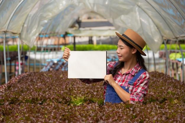 O jovem agricultor sorridente estava de pé em papel branco vazio.