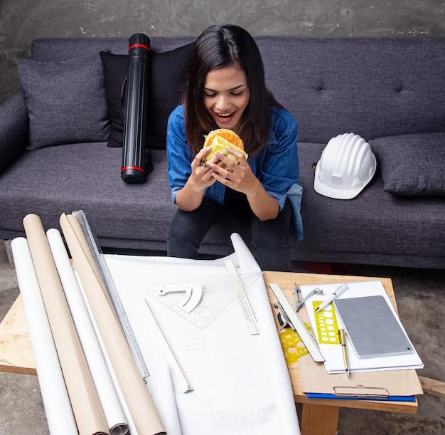 O jovem arquiteto bonito comendo hambúrguer entre trabalhar no projeto