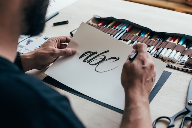 O jovem artista ilustrador hipster em uma camiseta preta simples cria um desenho autêntico e exclusivo de letras à mão em seu brilhante estúdio industrial