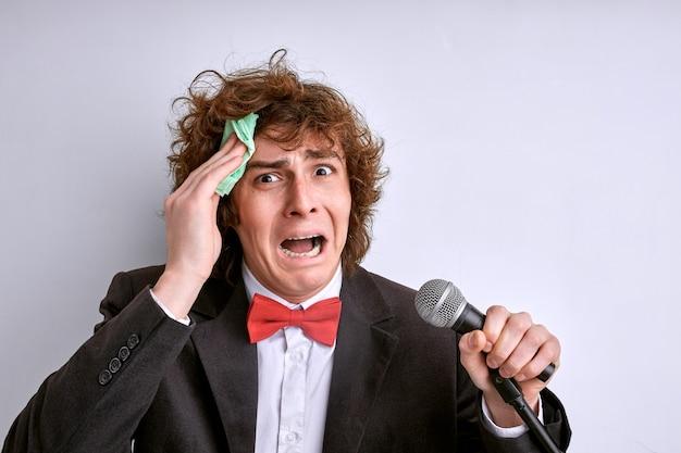 O jovem artista tem medo de errar durante a performance, ficar enxugando o suor da testa, se preocupar com falar mal, segurar o microfone. isolado no branco