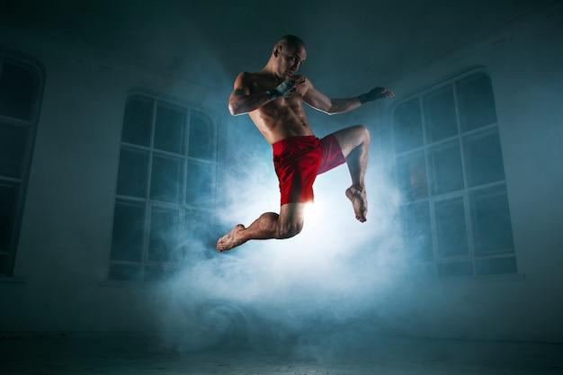 O jovem atleta do sexo masculino fazendo kickboxing em uma fumaça azul