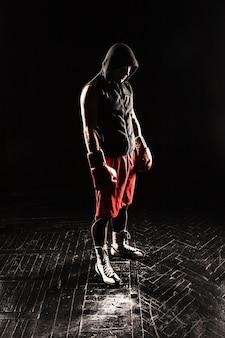 O jovem atleta masculino de kickboxing em pé contra um fundo preto