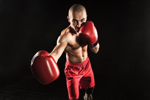 O jovem atleta masculino de kickboxing em um fundo preto