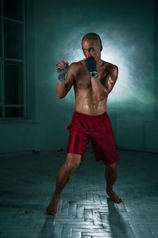 O jovem atleta masculino kickboxing em um fundo de fumaça azul