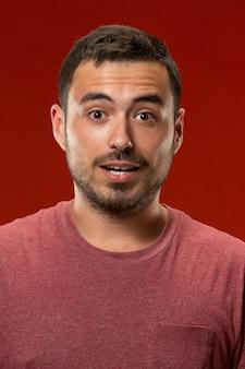 O jovem atraente olhando surpreso isolado no vermelho