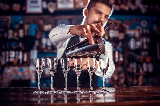 O jovem bartender surpreende com seus visitantes habilidosos em bares de coquetéis