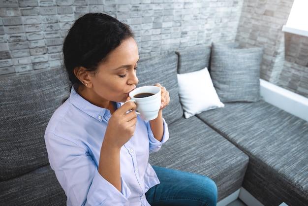 O jovem bebe café enquanto está sentado no sofá perto da janela.