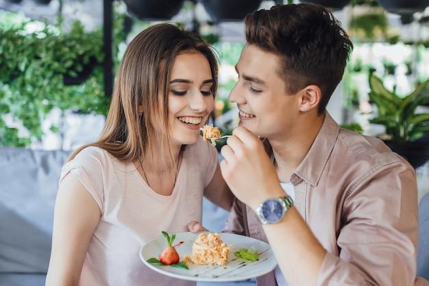 O jovem bonito alimenta sua mulher com um bolo delicioso