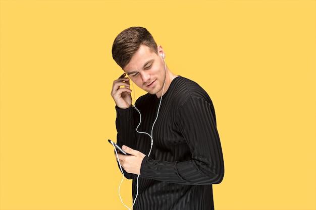 O jovem bonito em pé e ouvindo música.