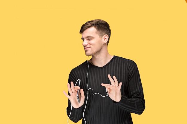 O jovem bonito em pé e ouvir música.