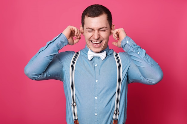 O jovem bonito emocional não suporta barulho, cobre os ouvidos com a ajuda de indicadores, parece estressado, usa gastadores azuis brancos listrados, gravata borboleta branca, camisa azul clara. copie o espaço para o anúncio.
