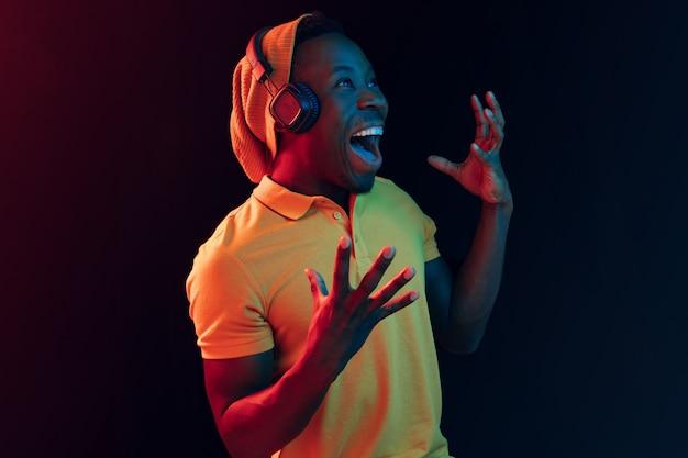 O jovem bonito feliz hippie ouvindo música com fones de ouvido no estúdio preto com luzes de néon