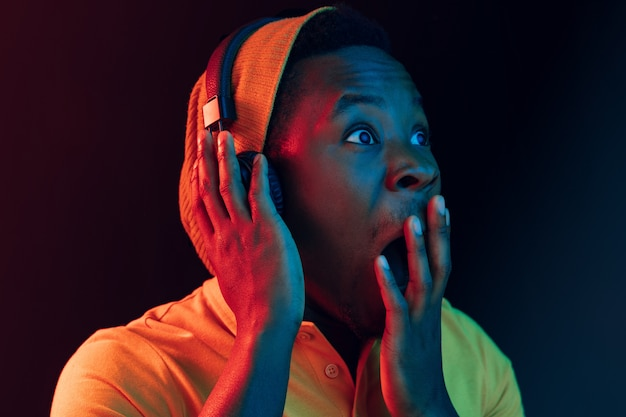 O jovem bonito feliz surpreso homem moderno ouvindo música com fones de ouvido no preto com luzes de néon