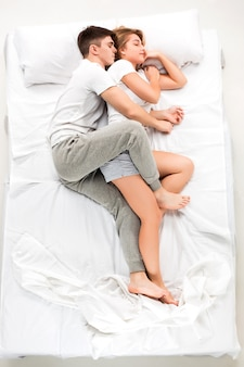 O jovem casal adorável, deitado em uma cama branca, amor lconcept, vista superior